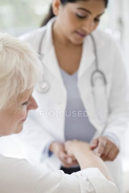 Female doctor examining senior patient arm. — Stock Photo