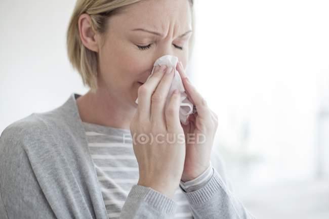 Metà di donna adulta che soffia il naso con il tessuto — Foto stock