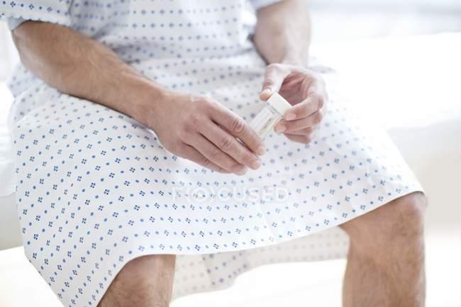 Paciente masculino en bata de hospital sentado en la cama sosteniendo el recipiente de muestra de orina . - foto de stock