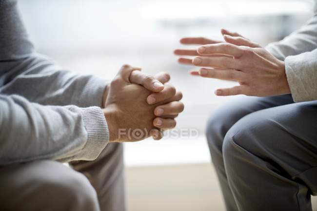 Cropped view of two people sitting face to face and gesturing with hands. — Stock Photo