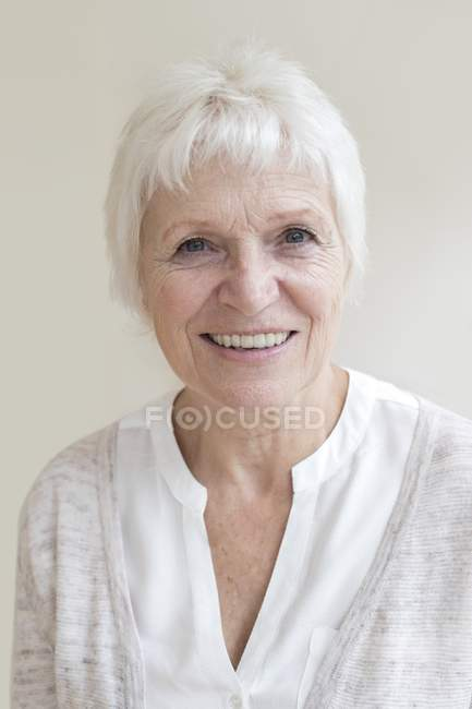 Femme Senior souriant et regardant à huis clos, portrait. — Photo de stock
