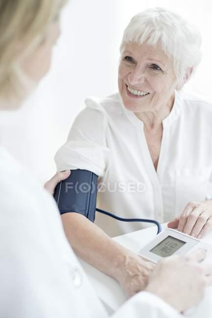 Ärztin nimmt Blutdruck von Seniorin. — Stockfoto