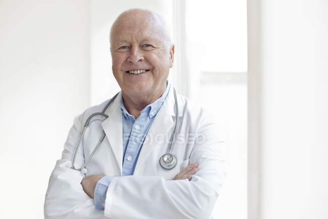 Senior male doctor with arms crossed smiling and looking in camera. — Stock Photo