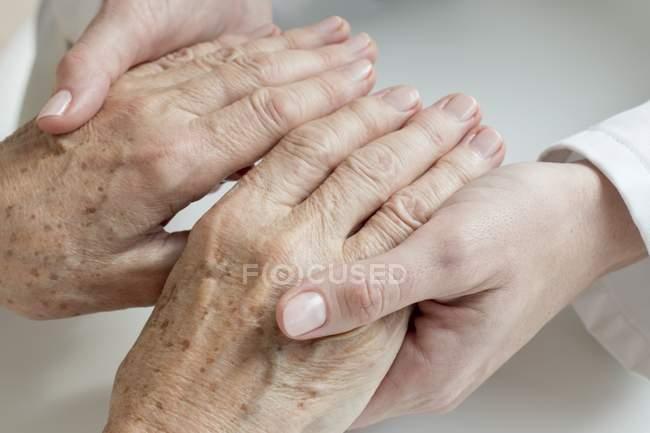Female doctor examining senior patient hands. — Stock Photo