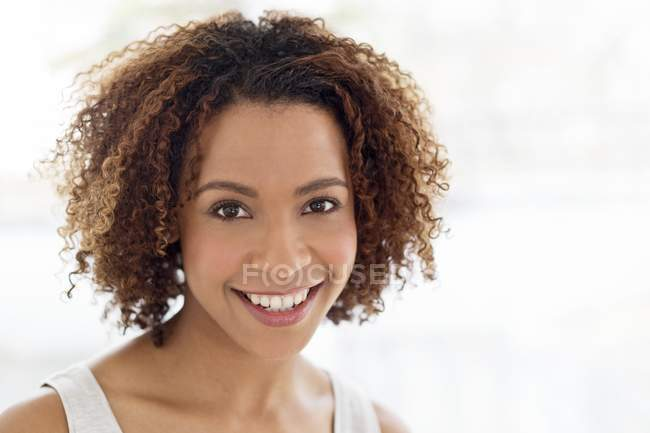Woman with curly hair smiling at camera — Stock Photo