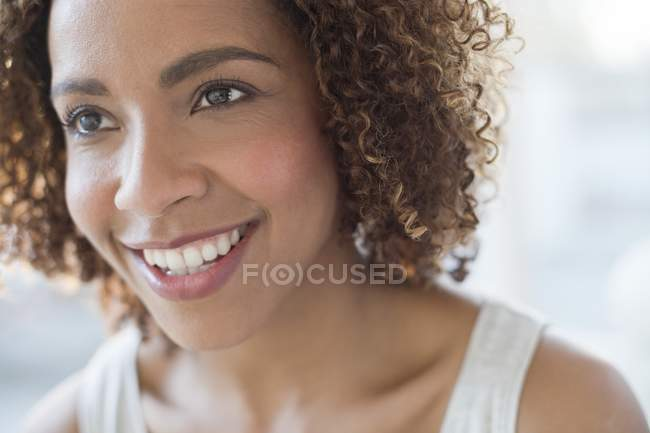 Счастливая женщина улыбается и смотрит в сторону — стоковое фото