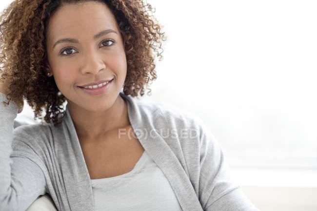 Mujer con el pelo rizado sonriendo a la cámara - foto de stock