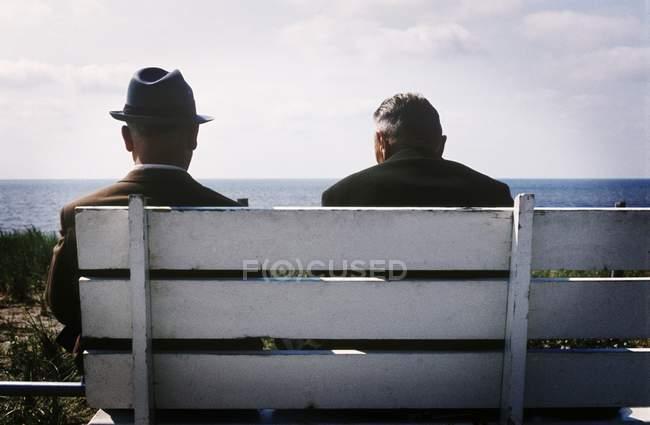 Двое мужчин сидят на скамейке — стоковое фото