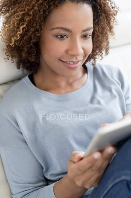 Femme utilisant une tablette numérique à la maison — Photo de stock