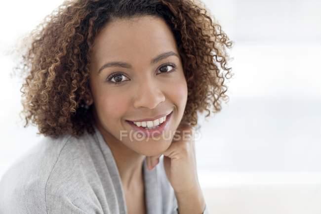 Жінка посміхаючись і, дивлячись на камеру — стокове фото