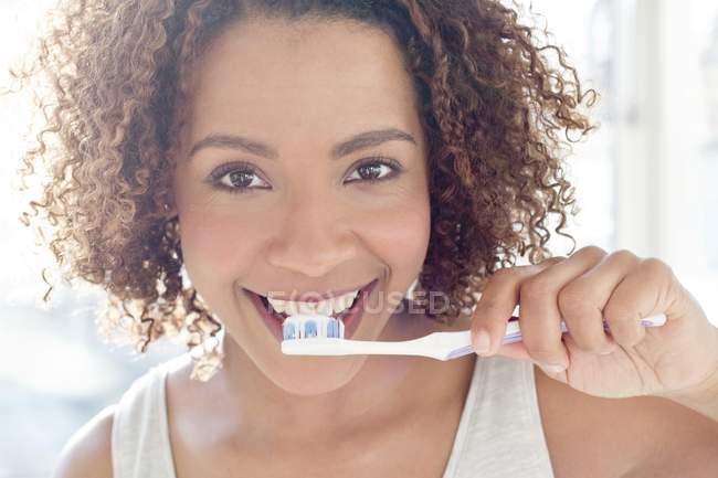 Woman brushing teeth and looking at camera — Stock Photo