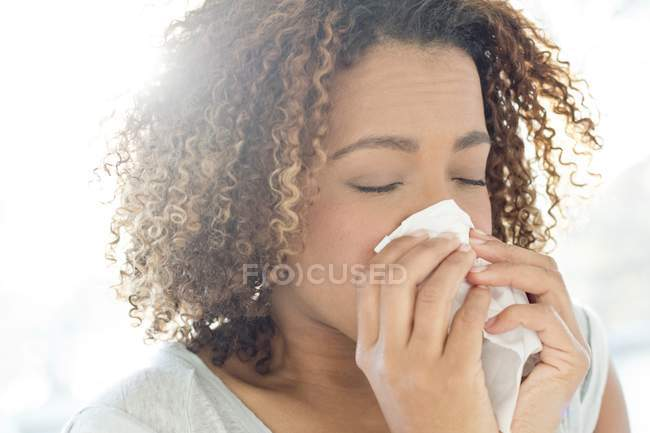 Woman blowing nose on tissue. — Stock Photo