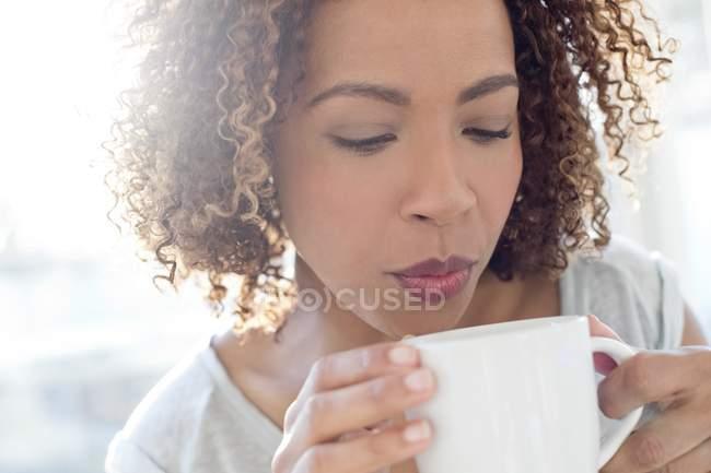 Женщина, дующая на кофе — стоковое фото