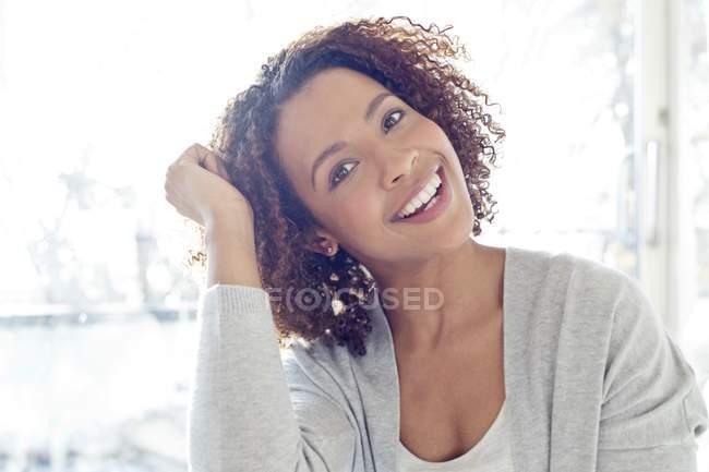 Женщина с вьющимися волосами улыбается в камеру — стоковое фото