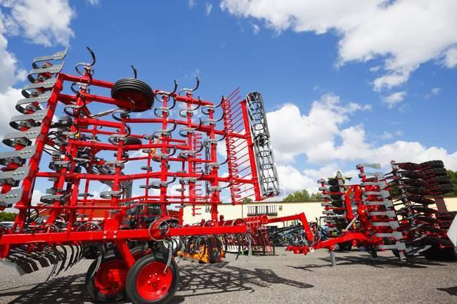 Rote Maschinen mit Cabriopflügen auf dem Hof. — Stockfoto