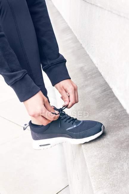 Обрізаний подання жіночих рук, пов'язуючи шнурків з ногою крок. — стокове фото