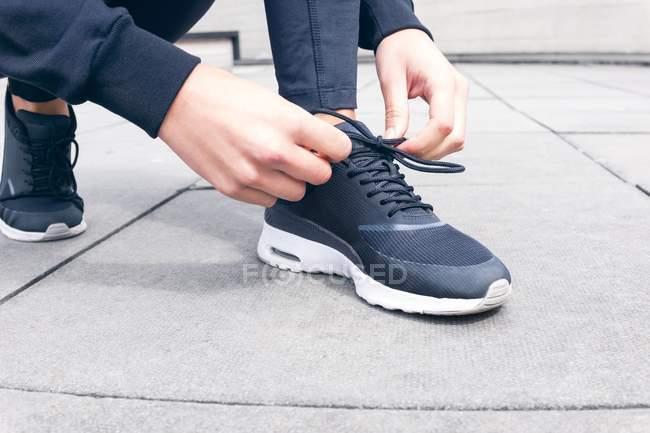 Recadrée vue des mains femmes attacher lacets sur trottoir — Photo de stock