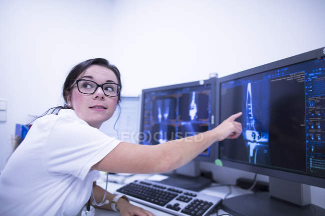 Hospital radiologist pointing at CT scans. — Stock Photo