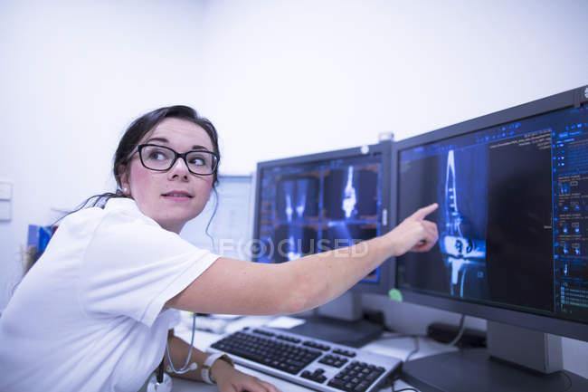 Radiologista do hospital apontando para tomografias computadorizadas . — Fotografia de Stock