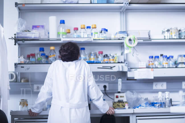 Female scientist leaning on desk in laboratory. — Stock Photo