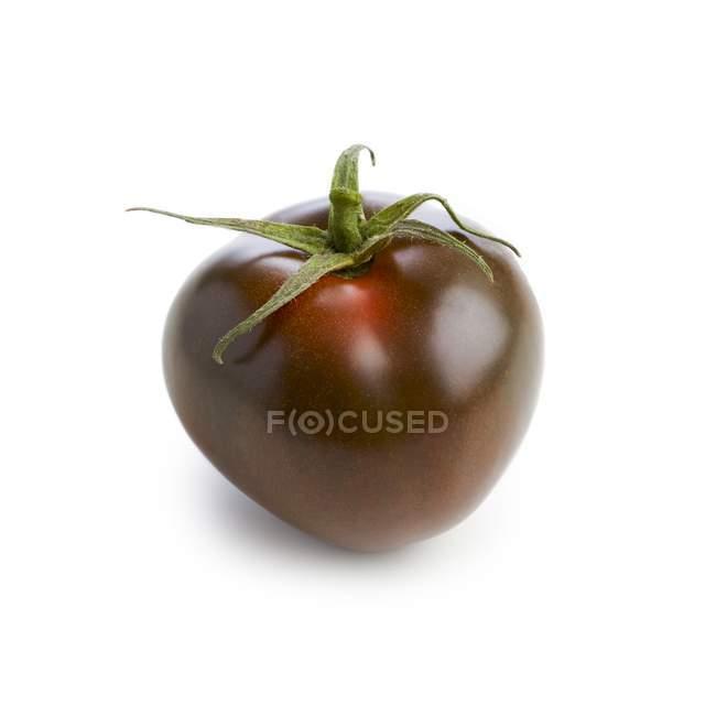 Чёрный помидор на белом фоне . — стоковое фото