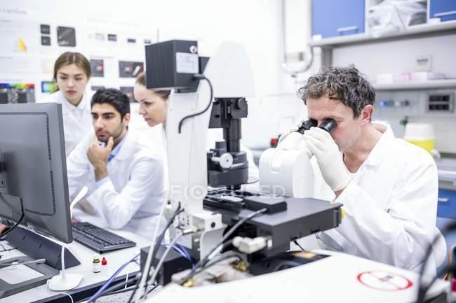 Scienziati che lavorano in laboratorio con computer e microscopio. — Foto stock