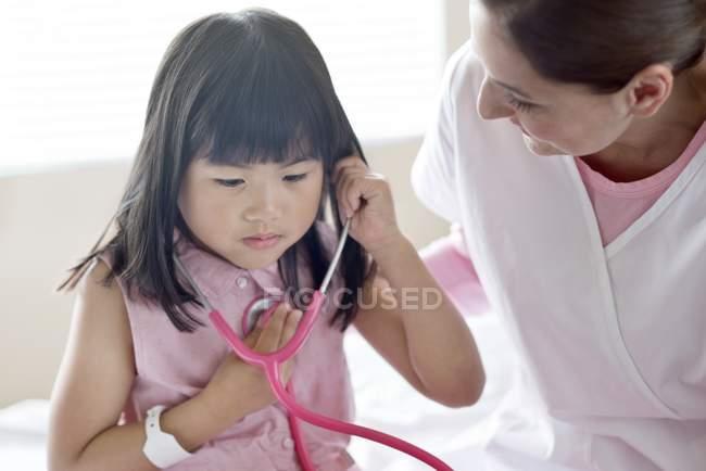 Азиатка использует стетоскоп с медсестрой . — стоковое фото