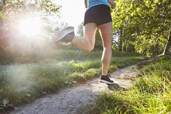 Young woman jogging on park path. — Stock Photo