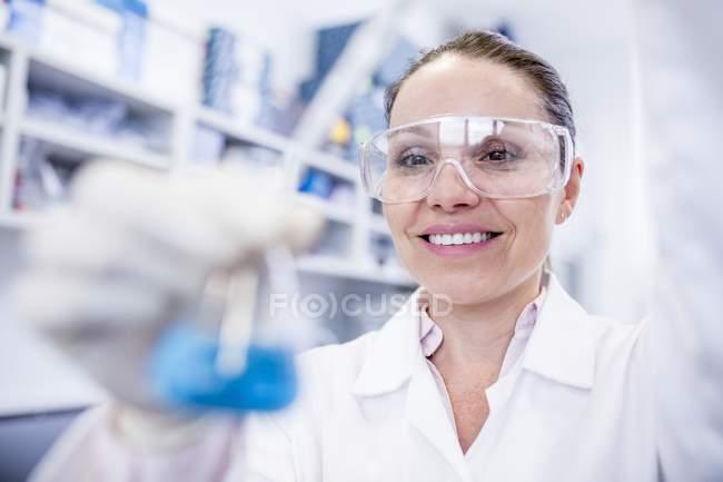 Female laboratory assistant using pipette. — Stock Photo