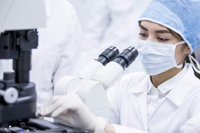 Female scientist in protective mask using microscope. — Stock Photo