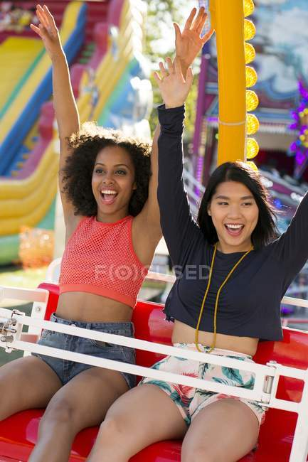 Two young women having fun on amusement ride. — Stock Photo