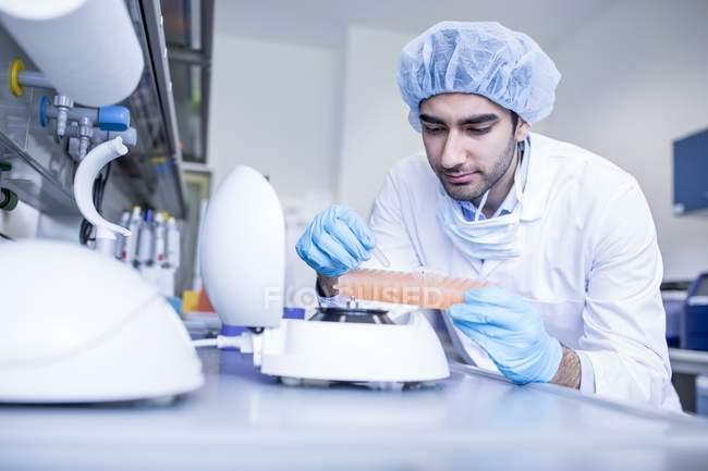 Ученый-мужчина в защитной одежде работает в лаборатории . — стоковое фото