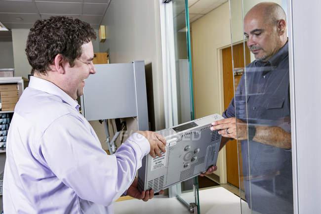 Trabajador de servicios dando el decodificador al cliente. - foto de stock