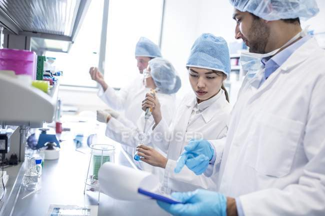 Scientists in protective clothing working in laboratory. — Stock Photo
