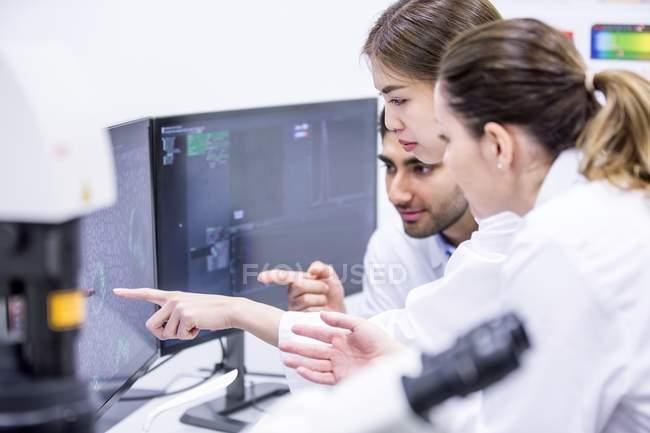 Wissenschaftler zeigen auf Computermonitor im Labor. — Stockfoto