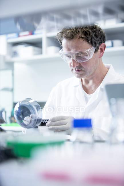 Male laboratory assistant using mini centrifuge. — Stock Photo