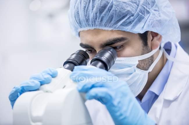 Wissenschaftler mit Operationsmütze unter dem Mikroskop. — Stockfoto
