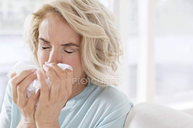 Donna matura soffiando naso sul tessuto . — Foto stock