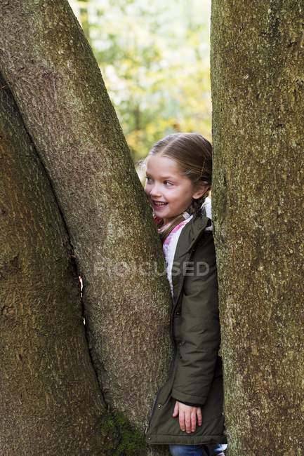 Menina a brincar de esconder-se atrás de troncos de árvore. — Fotografia de Stock