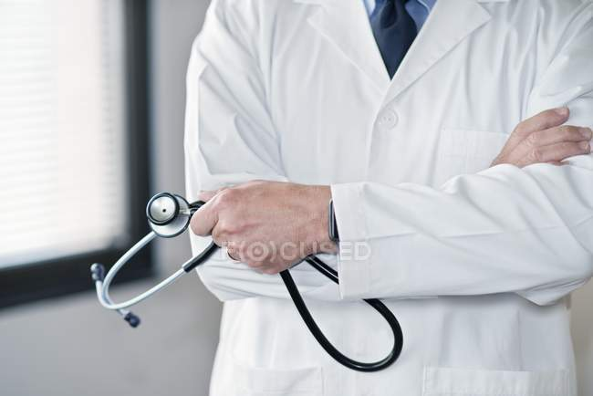 Male doctor in white coat with stethoscope and arms folded. — Stock Photo