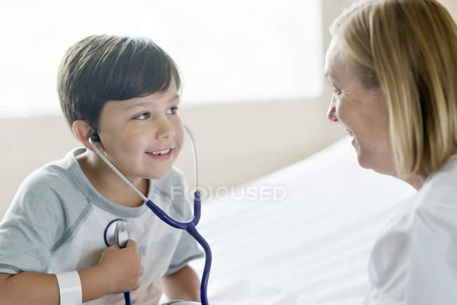 Niño jugando con estetoscopio con enfermera sonriente. - foto de stock