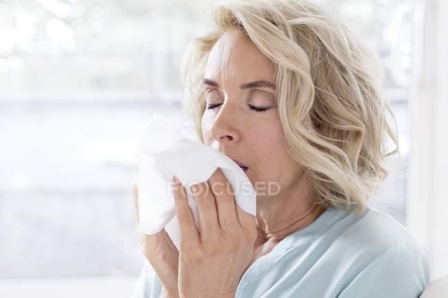 Зрілі жінки дме носом на тканині. — стокове фото