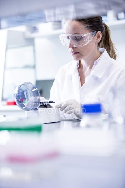Asistente de laboratorio femenina usando mini centrifugadora . - foto de stock