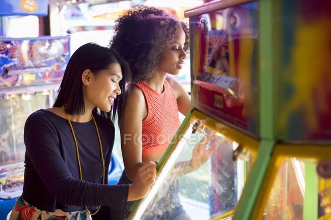 Freundinnen spielen Arcade-Spiel auf Kirmes. — Stockfoto