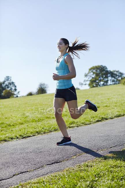 Молодая женщина бегает по парковой дорожке . — стоковое фото