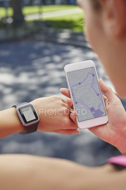 Femme, vérification des temps sur smartphone et sport smartwatch. — Photo de stock