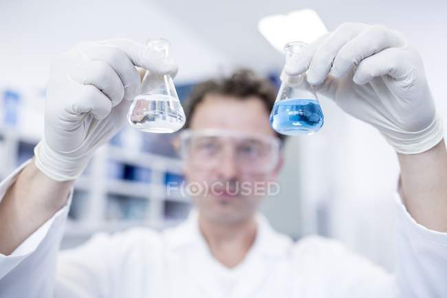 Male laboratory assistant holding chemical flasks. — Stock Photo