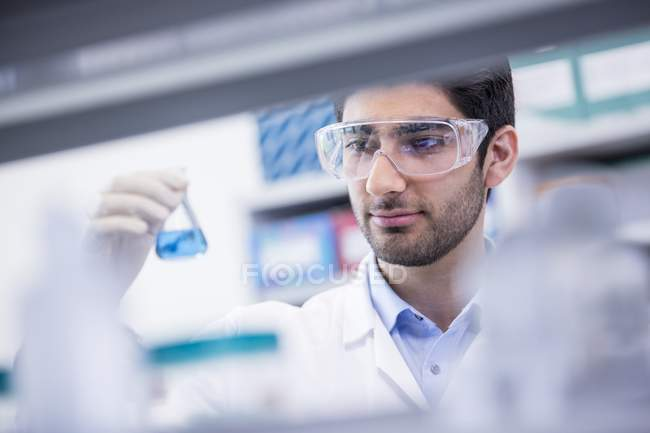 Laboratory assistant in safety goggles looking at chemical flask. — Stock Photo