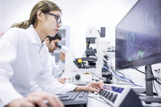 Ученые, использующие компьютер и микроскоп в лаборатории . — стоковое фото