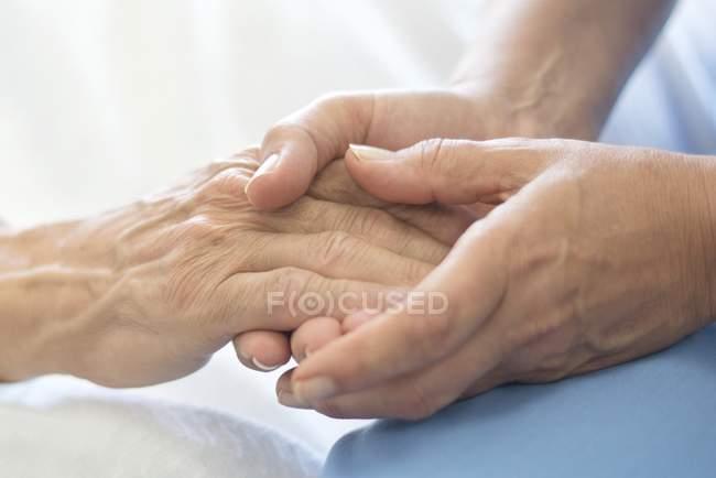 Krankenschwester hält männliche Patientenhand im Krankenhausbett. — Stockfoto